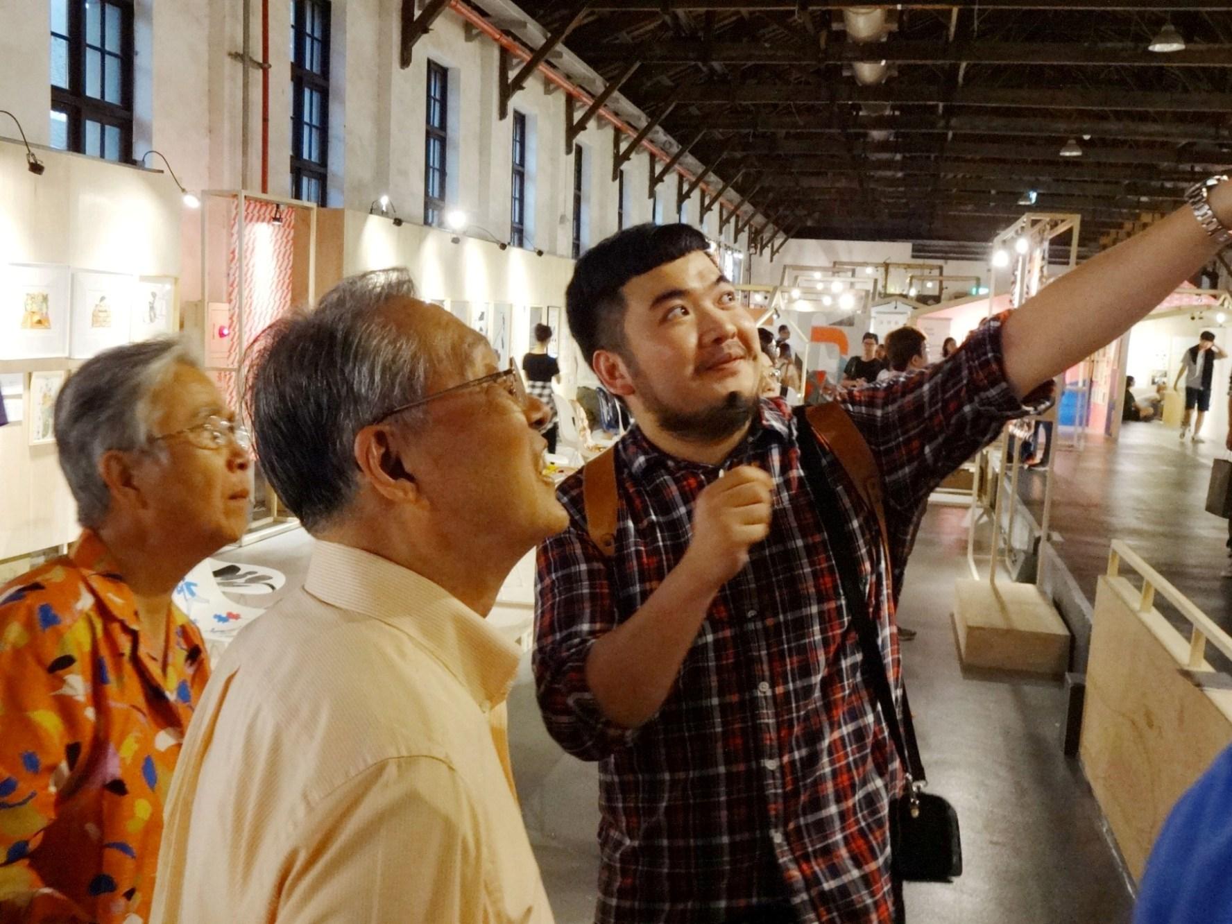 施振榮與夫人聆聽臺北風格1館VisualTaipei策展人鄒駿昇(右1)介紹國內外知名藝術家為臺北特別創作的畫作,聽得入神。